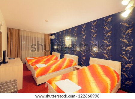 Interior of a hotel room for three persons, blue wallpapers and orange sheets on beds. - stock photo