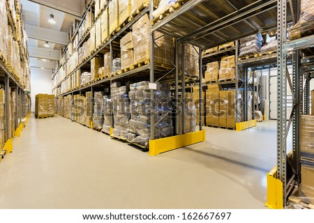 Interior of a huge spacious warehouse with carton boxes