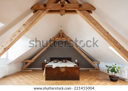 Interior of a loft or dormer bedroom in the apex of a roof with visible timber roof trusses , a patterned parquet floor and double bed - stock photo