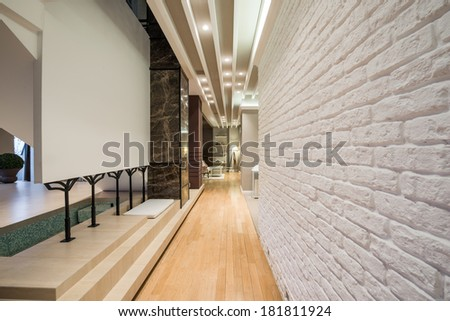 Interior of a long corridor with white brick wall - stock photo