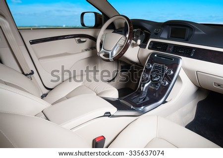 Interior of a modern automobile showing the dashboard with blue sky in the windows - stock photo