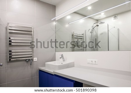 interior of a modern bathroom with a mirror, sink and heater