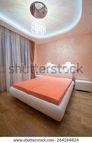 Interior of a modern bedroom with luxury ceiling lights - evening shoot  - stock photo