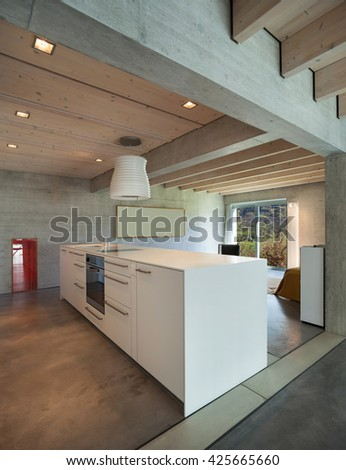 Interior of a modern chalet in cement, white kitchen island - stock photo