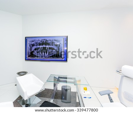 Interior Of A Modern Dental Office with fluorography on tv screen - stock photo