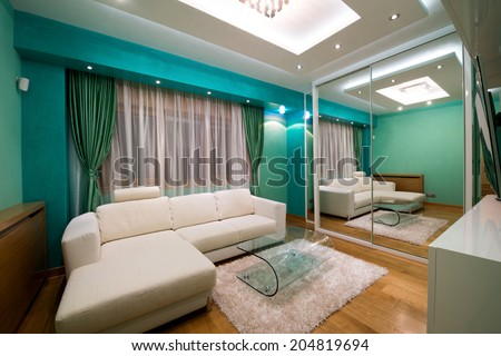 Interior of a modern green living room with luxury ceiling lights - stock photo