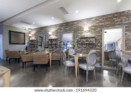 Interior of a modern hotel cafe with stone wall - stock photo