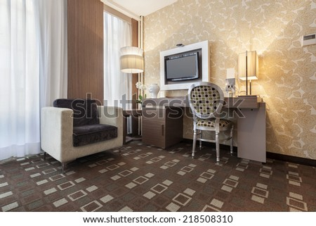 Interior of a modern hotel room with wall mounted tv - stock photo