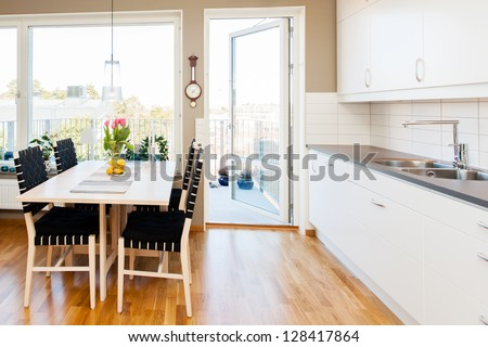interior of a modern kitchen with dining-table by the window and white cupboards - stock photo