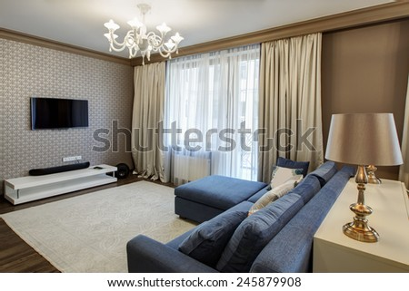 Interior of a modern living room with blue sofa in luxury mansion - stock photo