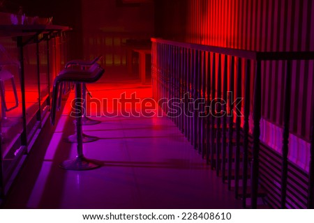 Interior of a nightclub with colorful red and purple lighting and a line of stylish bar stool along a reflective bar counter with a railing behind - stock photo