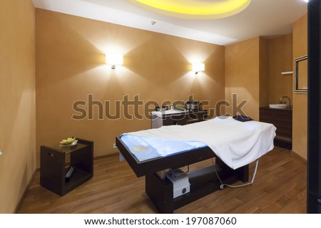 Interior of a room for stone massage with special therapeutic lights in massage bed - stock photo