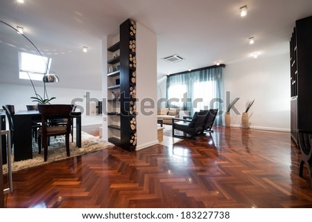 Interior of a spacious living room with logs for fireplace - stock photo