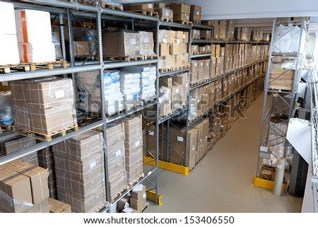 Interior of a spacious warehouse with metal stillage - stock photo