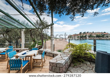 Interior of a summer terrace of restaurant. Sea view on islet Saint Stephen in Montenegro - stock photo