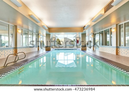 Interior of a swimming pool with Metal chrome plated ladder and tile flooring. Northwest, USA
