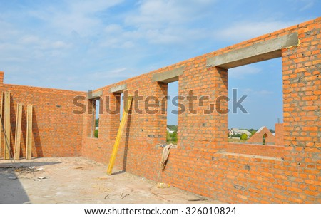 Interior of a Unfinished Red Brick House Walls under Construction without Roofing. Closeup on Attic Windows Hole Frame Construction - stock photo