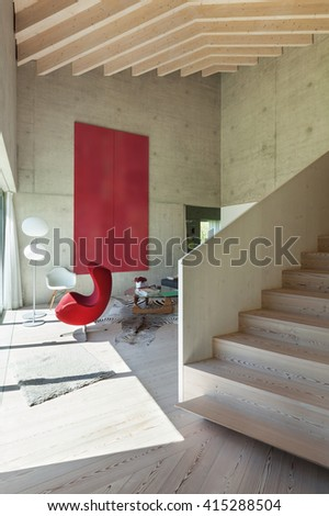 Interior of a villa, modern living room with red armchair. concrete walls - stock photo