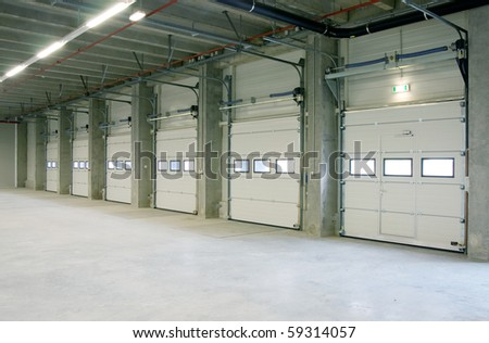 interior of a warehouse ,clean and empty, doors from loading docks - stock photo