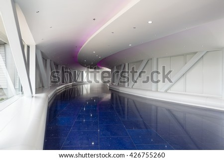 Interior of a white and blue modern pedestrian overpass  tunnel using led lights to simulate space travel. - stock photo