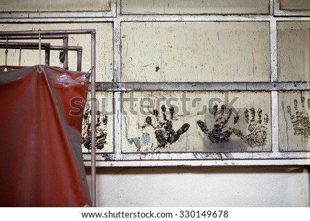Interior of abandoned industrial workshop with workers handprints on the walls and welding screens - stock photo