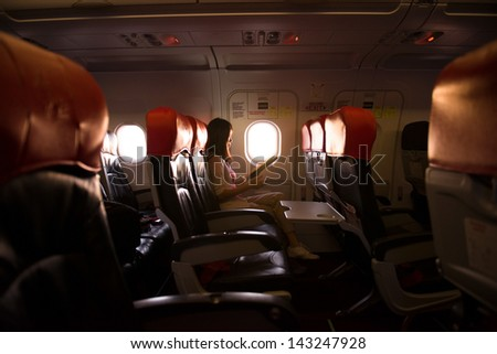 Interior of airplane with passenger reading on seats during a sunset, lowlight ambience mode