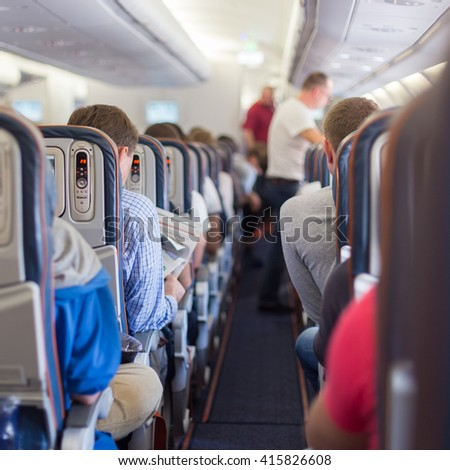 Interior of airplane with passengers during flight. Square composition.