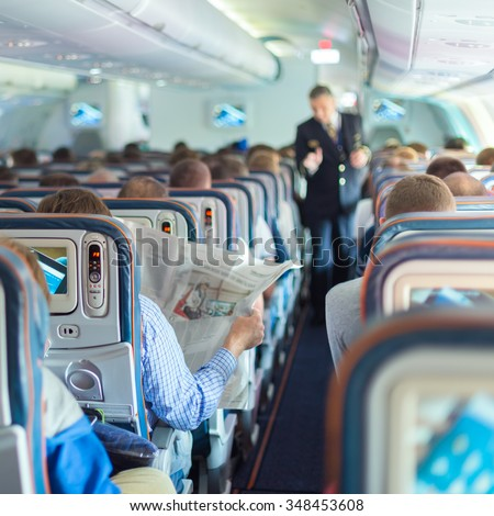 Interior of airplane with passengers on seats during flight. Steward in dark blue uniform walking the aisle. Square composition. - stock photo