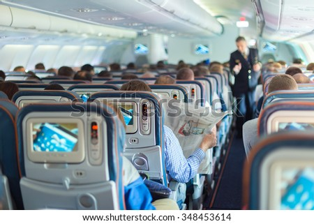 Interior of airplane with passengers on seats during flight. Steward in dark blue uniform walking the aisle. Horizontal composition. - stock photo