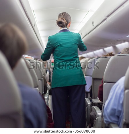 Interior of airplane with passengers on seats waiting to taik off. Stewardess in green uniform walking the aisle. Square composition.