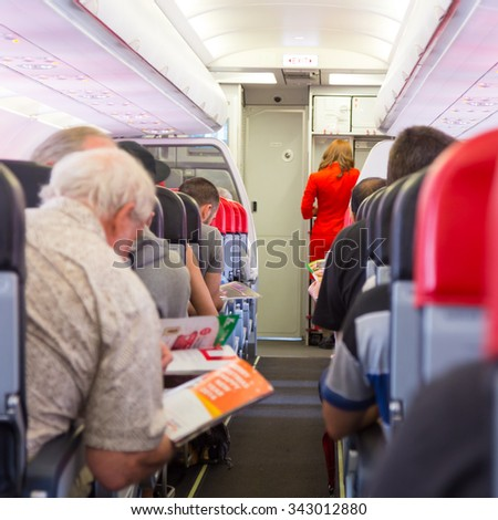 Interior of airplane with passengers on seats waiting to taik off. Stewardess in red uniform providing final instructions. Square composition. - stock photo