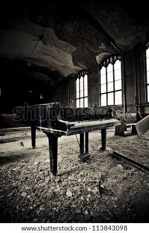 Interior of an abandoned school there is a grand piano that has been left to the ravages of time in Detroit Michigan . - stock photo