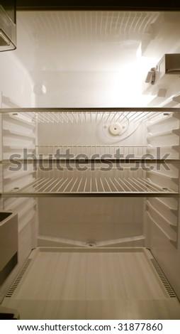 Interior of an empty fridge lit by the internal lamp - stock photo
