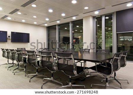 Interior of an empty modern conference room with TV screens, long table, chairs at night. Reflections of city skyscrapers in the office windows. - stock photo