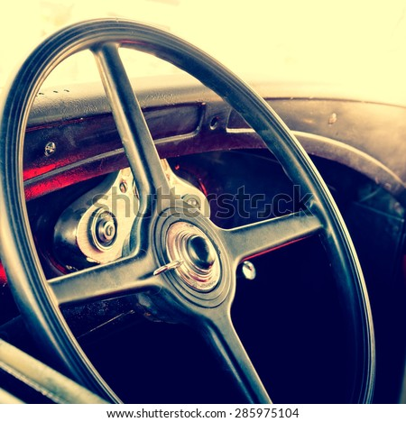Interior of an old automobile with steering wheel closeup. Retro car in soft light effect. Detail  of oldtimer automobile - vintage photo of inside car salon. - stock photo