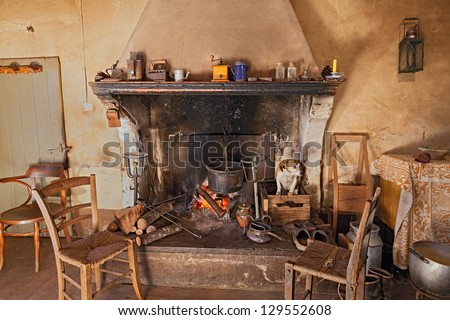 interior of an old country house where a dog gets hot inside the fireplace - stock photo