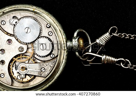 Interior of an old pocket watch on a black background showing part of the chain attached to the watch.