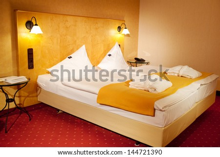Interior of arranged bed in hotel room - stock photo