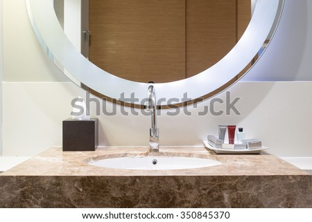 Interior of bathroom with washbasin faucet and white towel. - stock photo