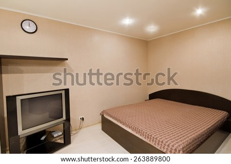 Interior of beige living room. Spacious studio apartment with double bed and TV - stock photo