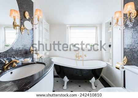Interior of black and white baroque bathroom - stock photo