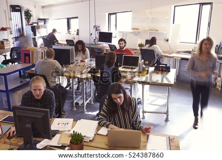 wide angle view busy design office. interior of busy design office with staff wide angle view j