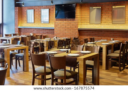 Interior of cafe-bar with wooden furniture and walls of bricks