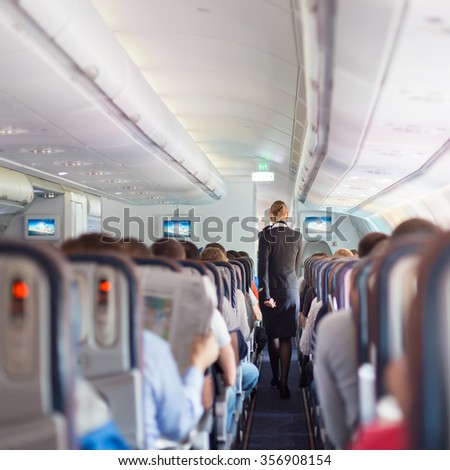 Interior of commercial airplane with passengers on seats during flight. Stewardess in dark blue uniform walking the aisle. Square composition.