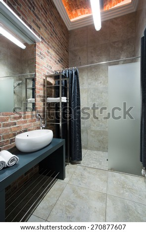 Interior of contemporary bathroom with brick wall