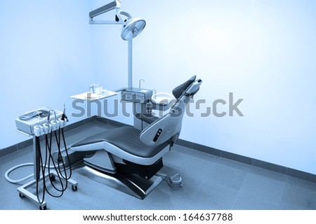 Interior of dental clinic with dental chair, dental tools and dental lighting equipment, BLUE TONE - stock photo
