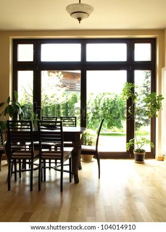 Interior of dining room overlooking the garden - stock photo