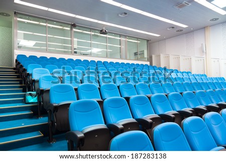 Interior of empty conference hall with blue velvet chairs. - stock photo