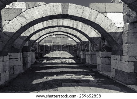 Interior of empty corridor with arcs. Ruins of Ancient city Smyrna. Izmir, Turkey. Black and white photo - stock photo