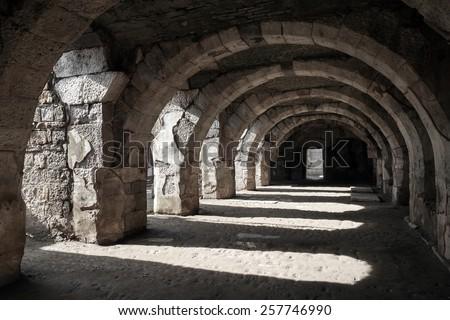 Interior of empty dark corridor with arcs. Ruins of Ancient city Smyrna. Izmir, Turkey - stock photo
